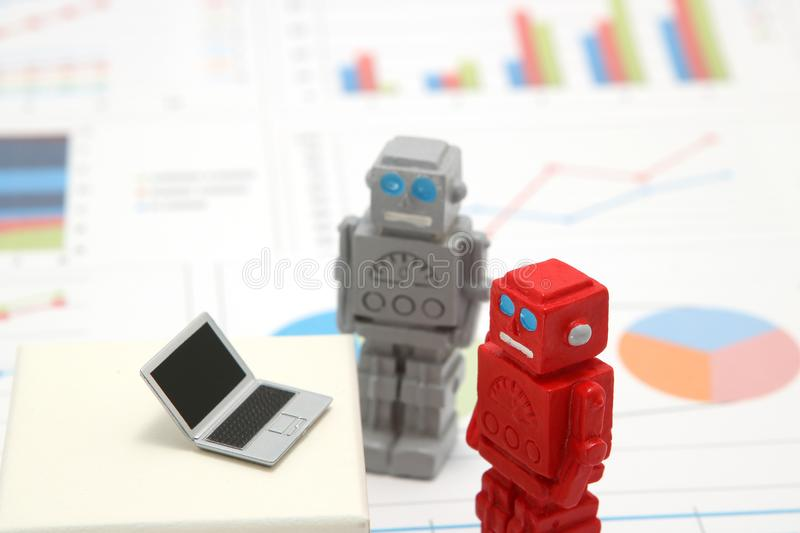 Robots or artificial intelligence and laptop on graphs and charts. Concept of artificial intelligence. Robots or artificial intelligence and laptop on graphs royalty free stock photography
