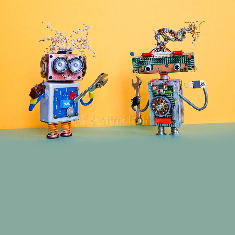 Robots automation maintenance service concept. Handyman robotic characters with hand wrench and pliers. Yellow wall royalty free stock image