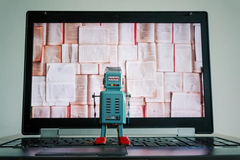 Robots with books screen, big data and deep learning concept. Robots looking at laptop screen with open books, artificial intelligence, big data and deep stock photography