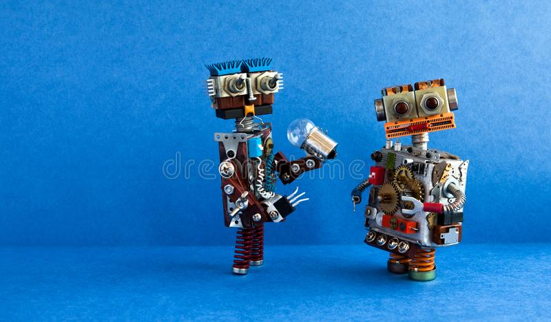 Robots communication, artificial intelligence concept. Two robotic characters, light bulb. Creative design toys on blue. Background. copy space royalty free stock image