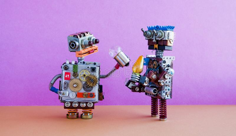 Robots communication, artificial intelligence concept. Two robotic characters with light bulbs. Creative design toys on stock images