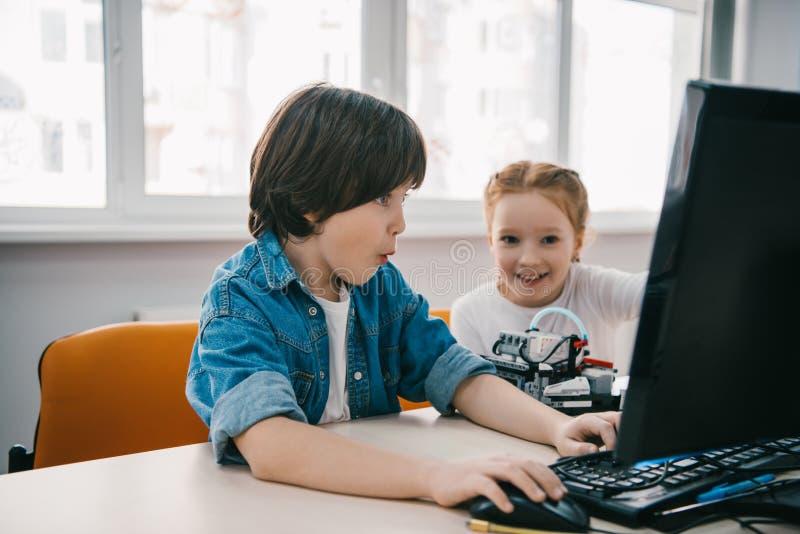 robots de programación emocionados de los niños junto, tronco fotos de archivo libres de regalías