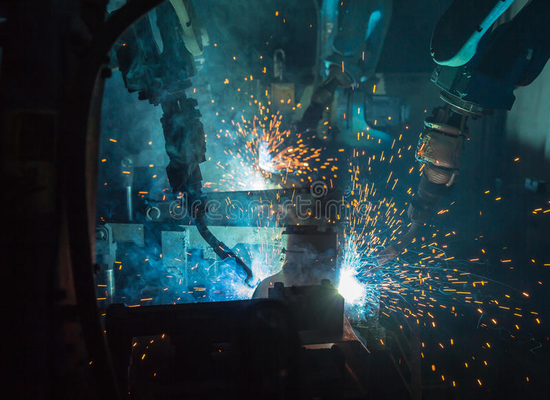 Robots que sueldan con autógena en una fábrica del coche imagen de archivo