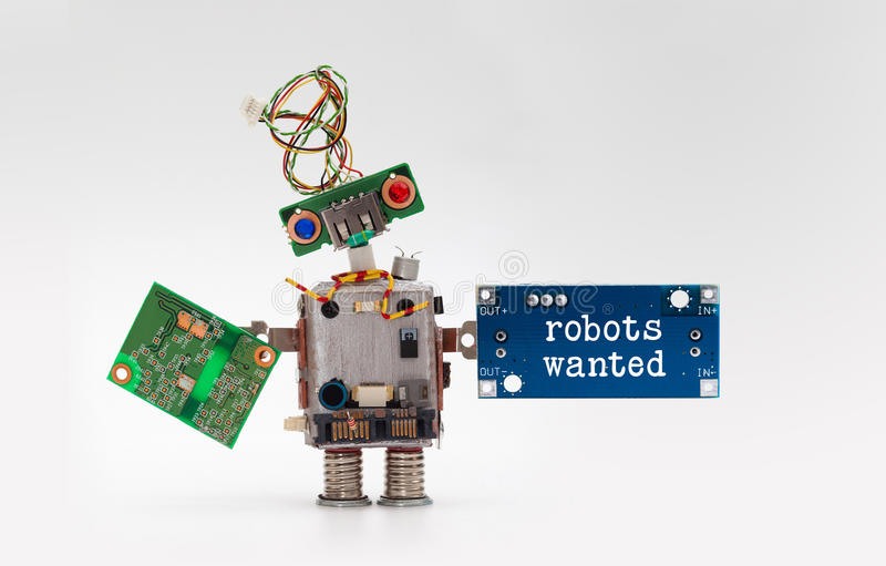 Robots wanted electronic wokers hiring concept. Toy robotic character handing circuit micro chip circuits on gray. Background stock photo