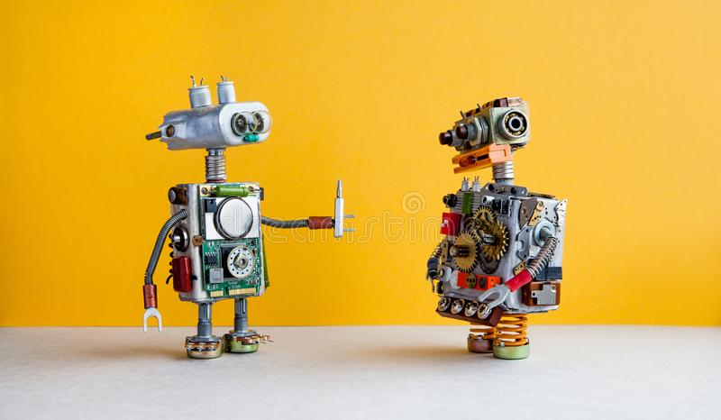 Robots on yellow background. 4th industrial revolution automation concept. Robotic serviceman with screwdriver, creative. Design cyborg toys. Maintenance repair stock photos