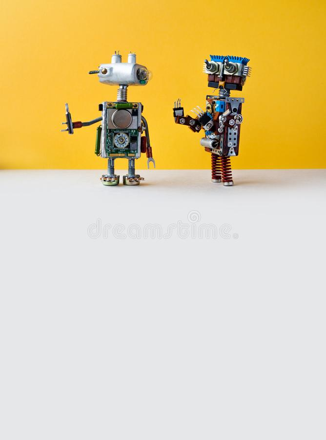 Robots on yellow background. 4th industrial revolution automation concept. Robotic serviceman with screwdriver, creative. Design cyborg toys. Maintenance repair royalty free stock photo