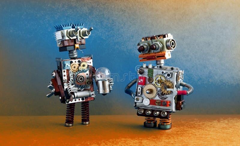 Robotsmededeling, kunstmatige intelligentieconcept Twee robotachtige karakters met gloeilamp stock foto's
