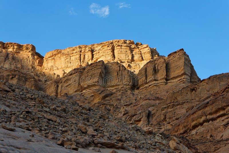 Roca de oro en el desierto en la puesta del sol imagenes de archivo