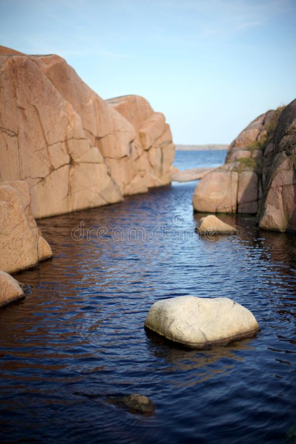 Roca en agua con fuera de los acantilados del foco en el fondo fotos de archivo libres de regalías