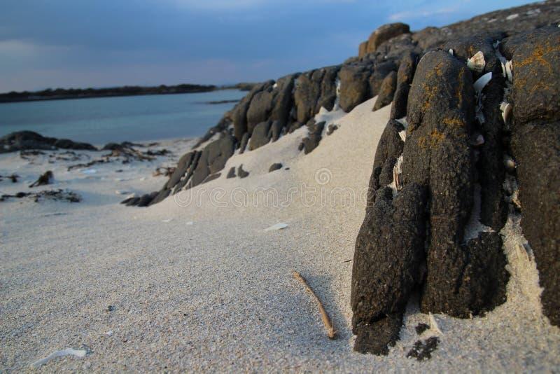 Roca en la playa arenosa imagenes de archivo