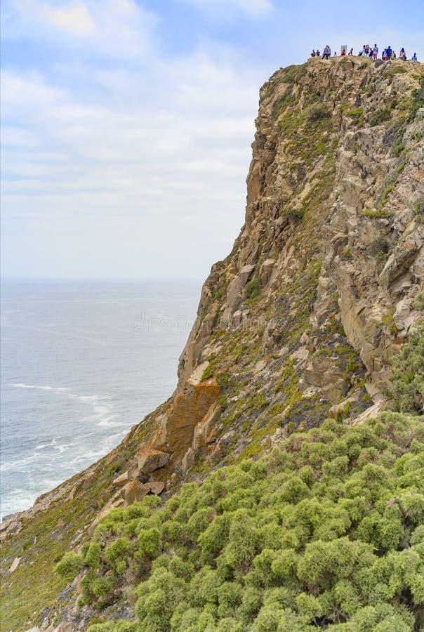 roca f?r caboda portugal Fyr och klippor över Atlanten Cabo da Roca över klipporna med små turister arkivfoto