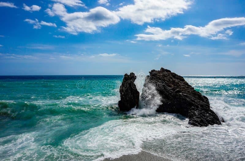 Roca grande en el mar mediterrean entre las ondas que estrellan una onda grande imagen de archivo