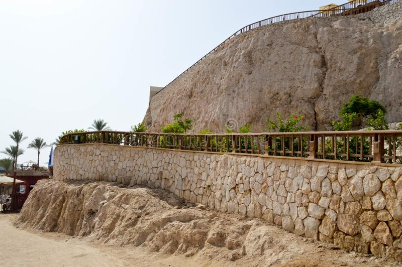 Roca hermosa con una pared de piedra de guijarros y de la barandilla amarillos viejos, antiguos contra el cielo azul y las palmer imagenes de archivo