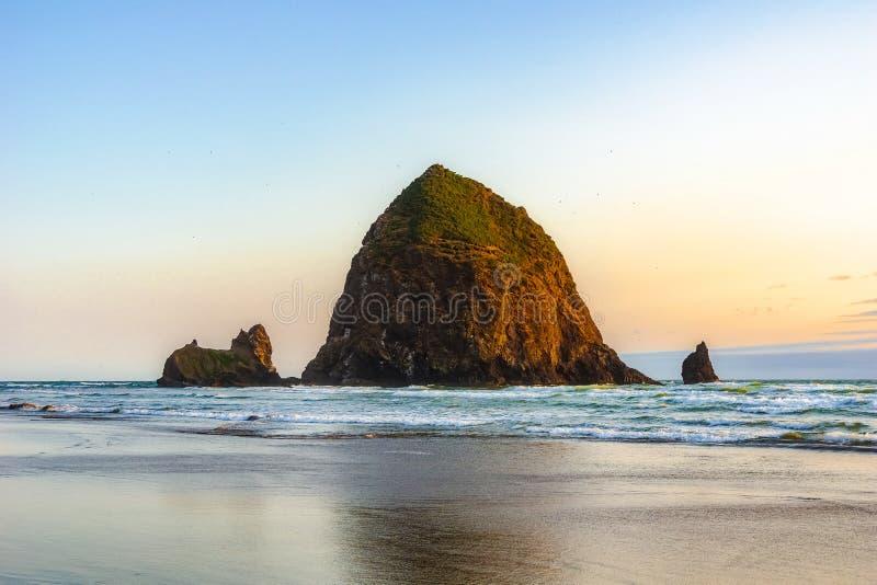Roca hermosa del pajar, señal natural famosa de la Costa del Pacífico, en la puesta del sol, playa del cañón, costa de Oregon fotos de archivo