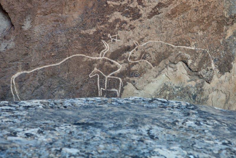 Roca-pintura prehistórica de los petroglifos de QOBUSTAN en Azerbaijan imagenes de archivo