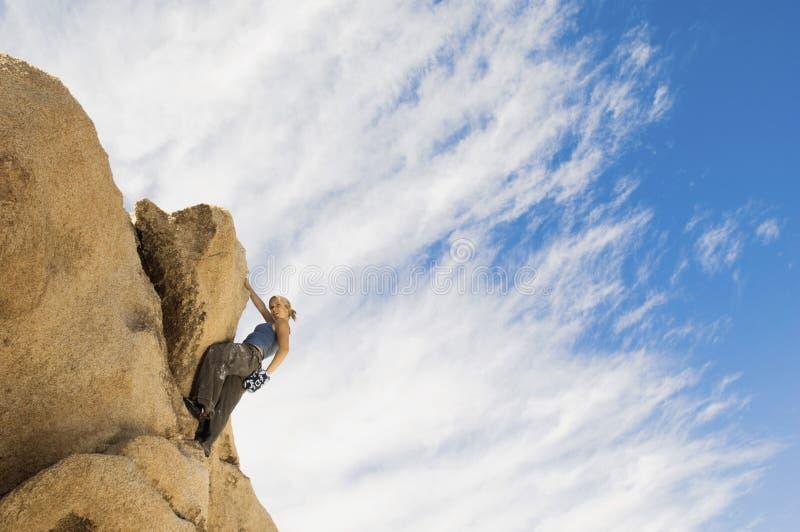 Roca que sube de la muchacha contra el cielo nublado fotografía de archivo libre de regalías