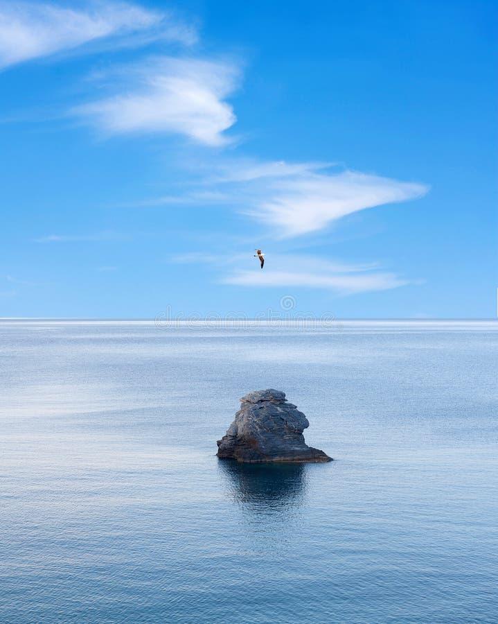 Roca solitaria sobre el mar tranquilo y pájaro de vuelo sobre el cielo azul imágenes de archivo libres de regalías