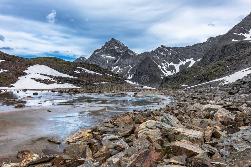 Rocas, agua y arena aluvial en un pequeño valle de la montaña imagen de archivo libre de regalías