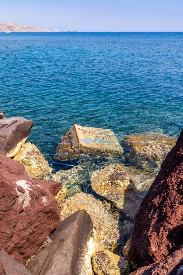 Rocas contra un océano coloreado azul, isla del santorini, Grecia fotografía de archivo