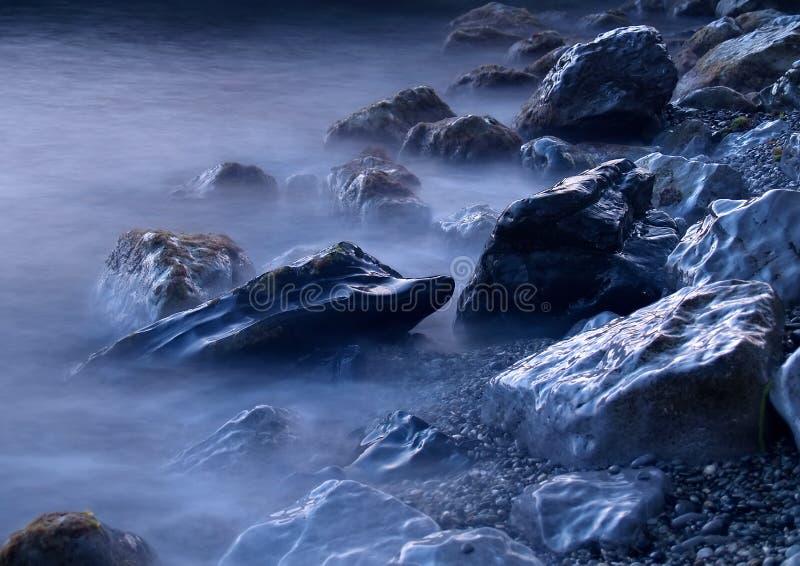 Rocas del mar en niebla imagenes de archivo