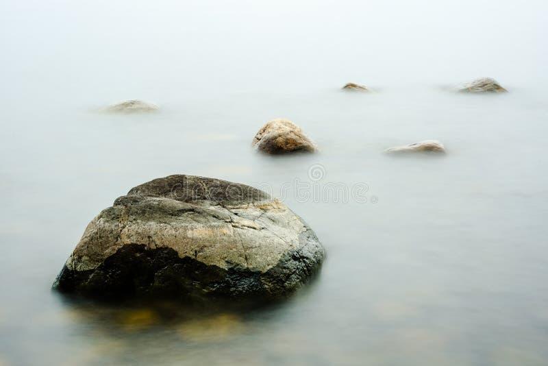 Rocas en el agua de la niebla imagenes de archivo