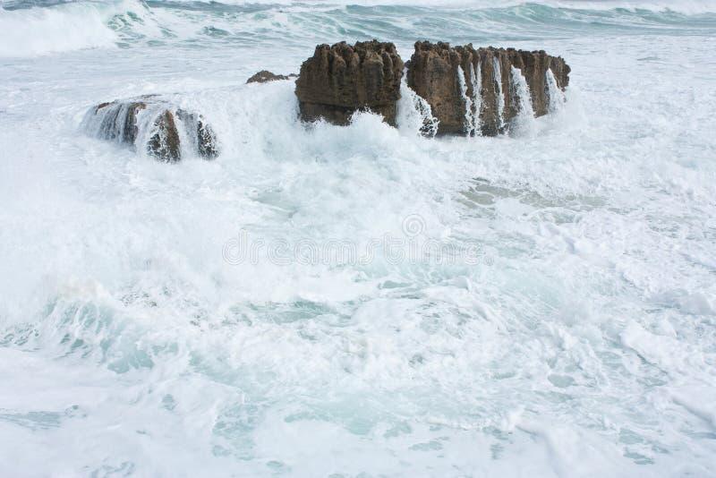 Rocas en el mar lavado encima por las ondas en el gran camino del océano en Australia imagen de archivo