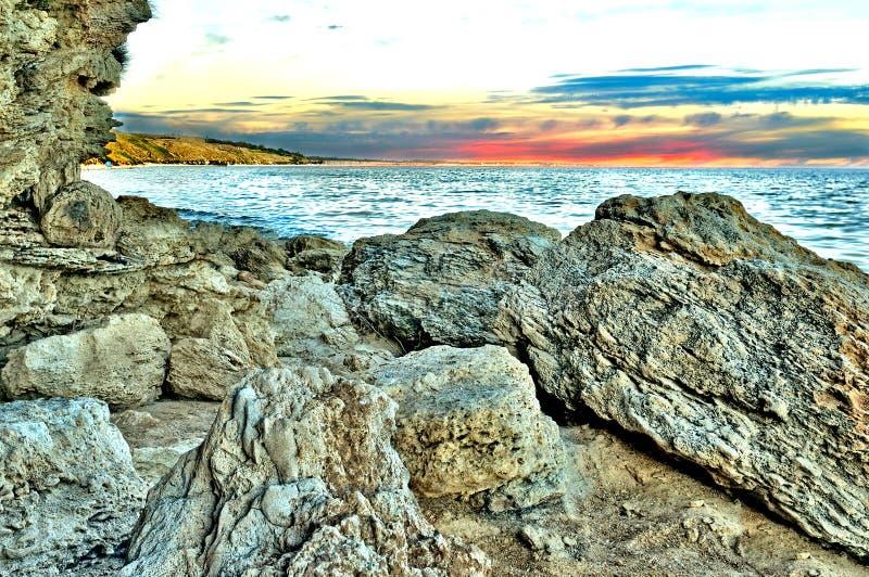 Rocas en el primero plano en el fondo del mar y del zakata imagen de archivo