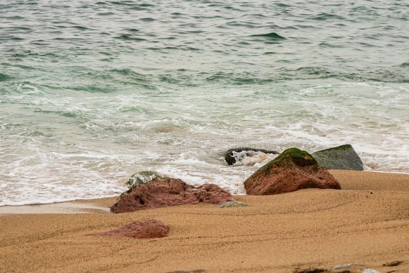 Rocas en la arena arrastrada por las olas en Puerto Vallarta, México foto de archivo