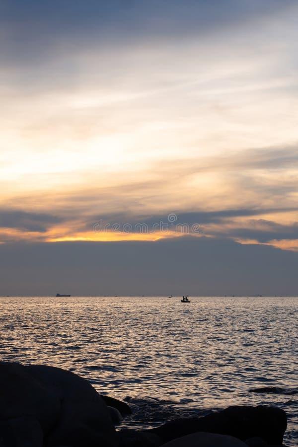 Rocas en la arena y los pescadores en pequeños barcos de pesca en el fondo de la puesta del sol, silueta fotografía de archivo libre de regalías