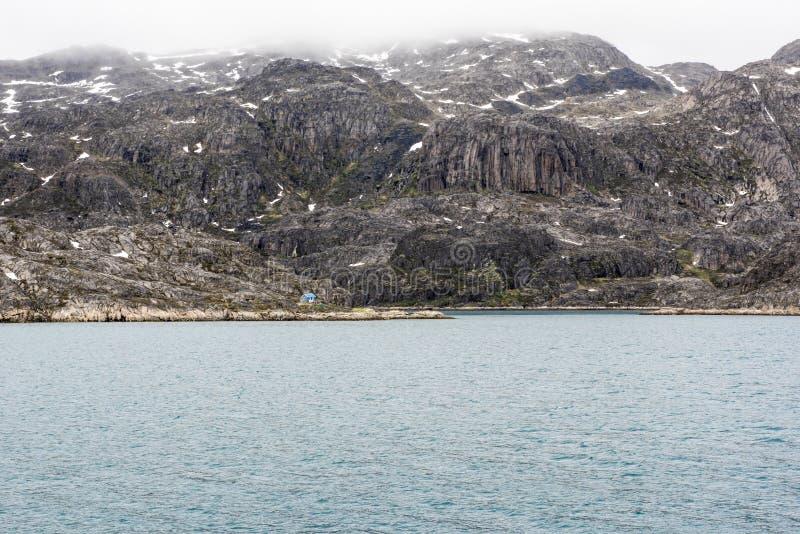Rocas enormes, pequeña casa, Groenlandia fotos de archivo