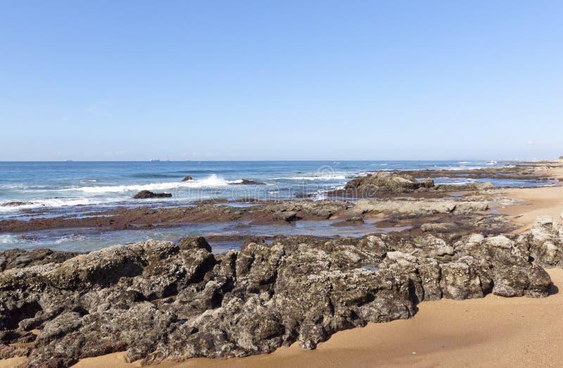 Rocas expuestas durante la bajamar, playa Durban Suráfrica de Umdloti imagen de archivo
