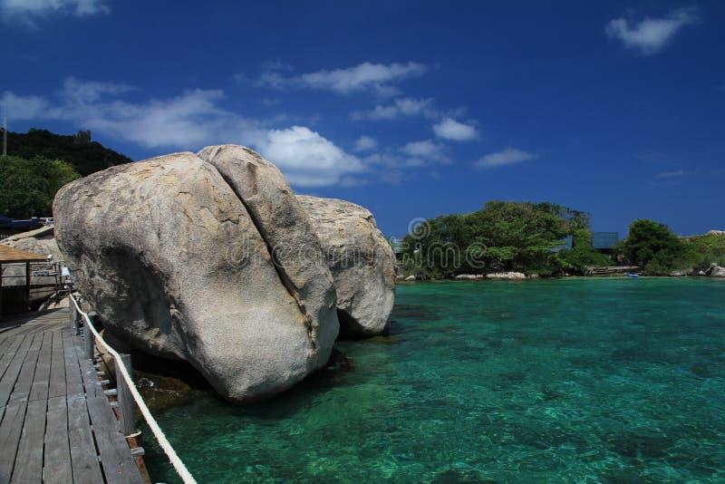 Rocas gigantes en la agua de mar fotos de archivo