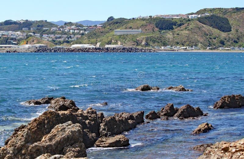 Rocas hechas punta al borde de la bahía de Lyall en Wellington, Nueva Zelanda Los edificios del aeropuerto se pueden apenas ver e fotografía de archivo libre de regalías