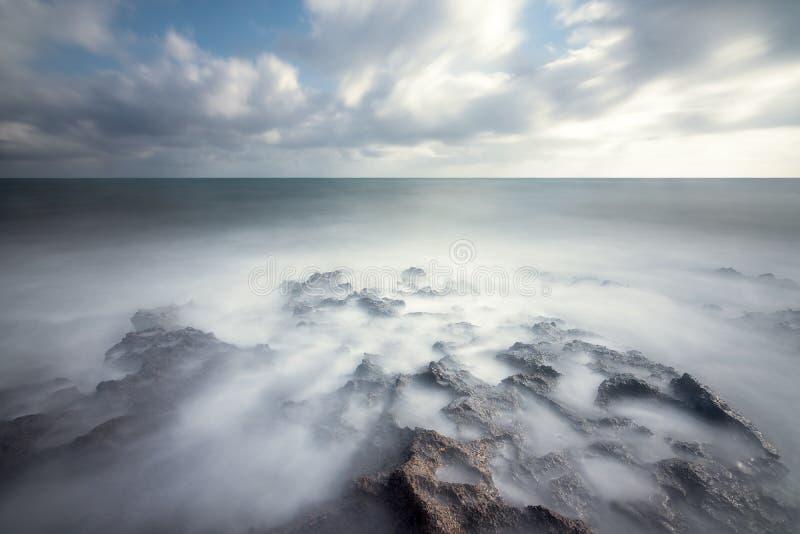 Rocas idílicas bañadas por un mar etéreo bajo un paisaje nublado espectacular fotografía de archivo libre de regalías