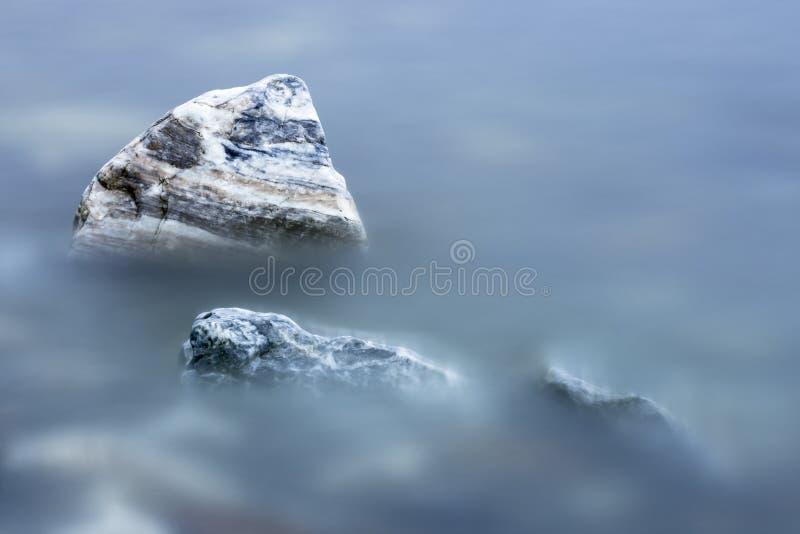 Rocas rayadas en agua azul lisa foto de archivo
