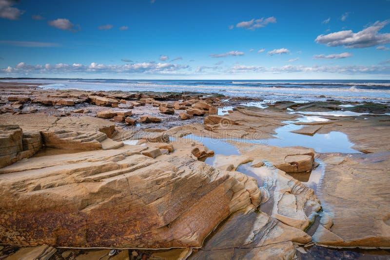 Rocas resistidas mar en la bahía de Druridge fotos de archivo libres de regalías