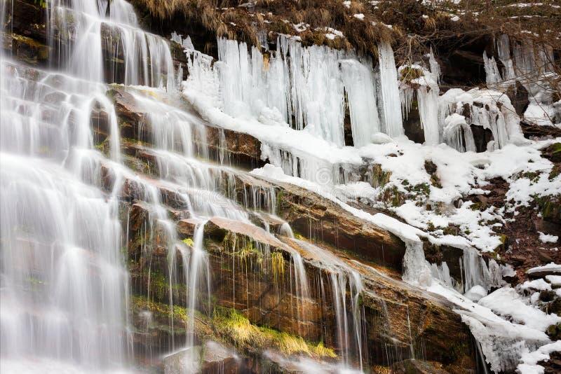 rocas rojas ascendentes y iluminadas por el sol de Tupavica del cierre colorido Semi-congelado de la cascada e hierba amarilla imagenes de archivo