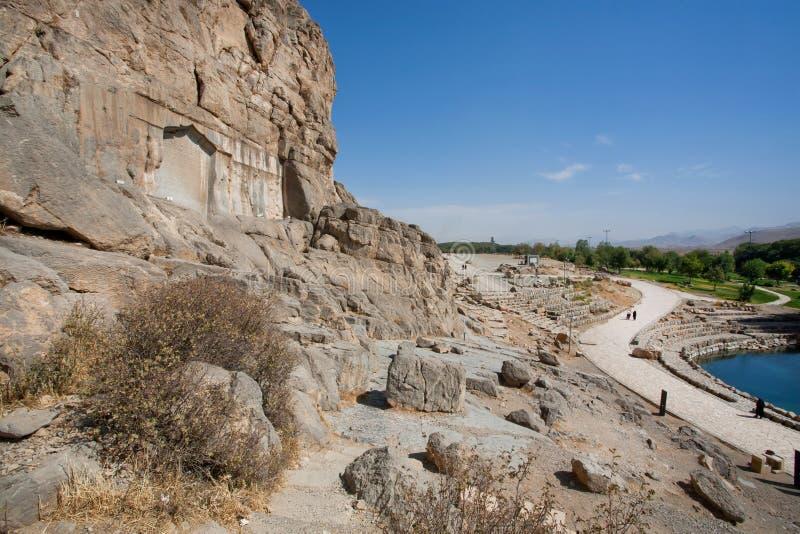 Rocas sobre el lago y alivios de piedra antiguos en el valle persa con el camino rural fotos de archivo libres de regalías
