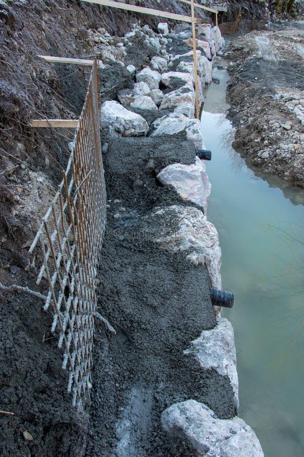 Rocas y hormigón grandes en la orilla del río foto de archivo