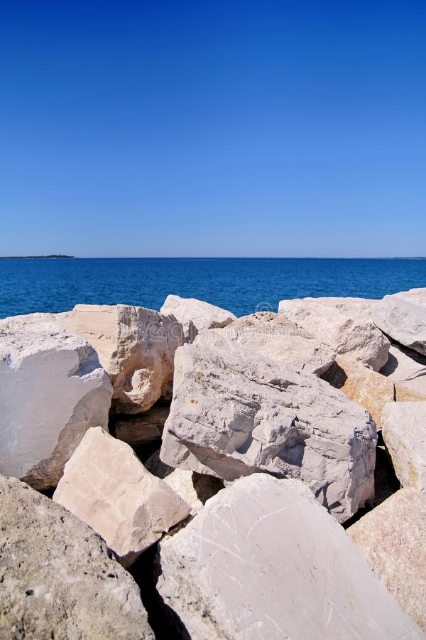 Rocas y piedras blancas con el mar y el cielo imagen de archivo