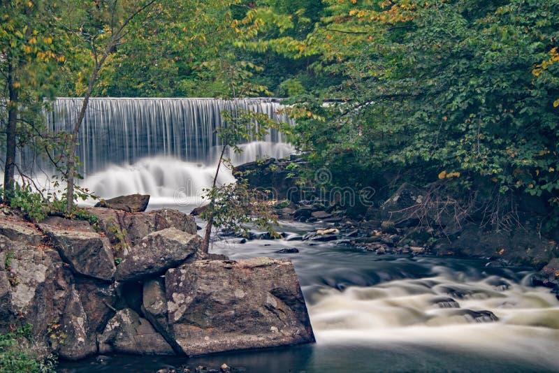 Rocas y rápidos con la presa del molino en el fondo imagenes de archivo