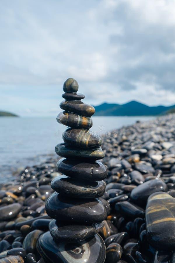 Rocce brillanti e lucidate accatastate su sulla riva con molti rocce/ciottoli lucidati su un'isola in Tailandia immagine stock