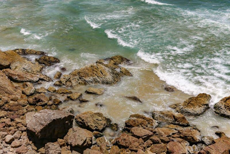 Rocce che conducono fuori alle onde in acqua verde smeraldo dell'oceano immagine stock