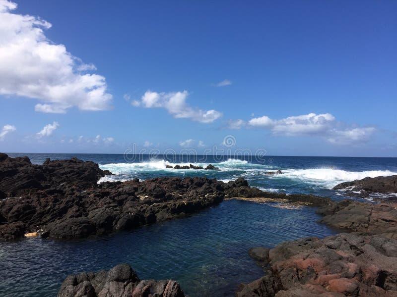 Rocce di Brown accanto all'oceano con la bolla Wave sotto cielo blu fotografia stock libera da diritti