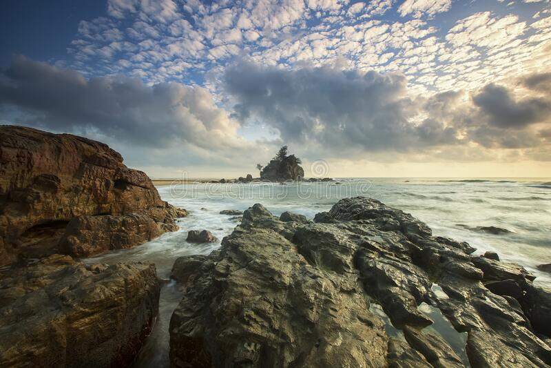 Rocce di Brown sulla spiaggia sotto il cielo bianco della nuvola fotografia stock libera da diritti