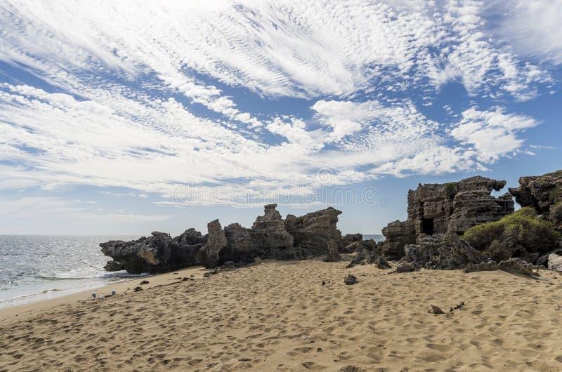 Rocce esposte al vento sull'isola contro un cielo drammatico, Rockingham, Australia occidentale del pinguino fotografie stock libere da diritti