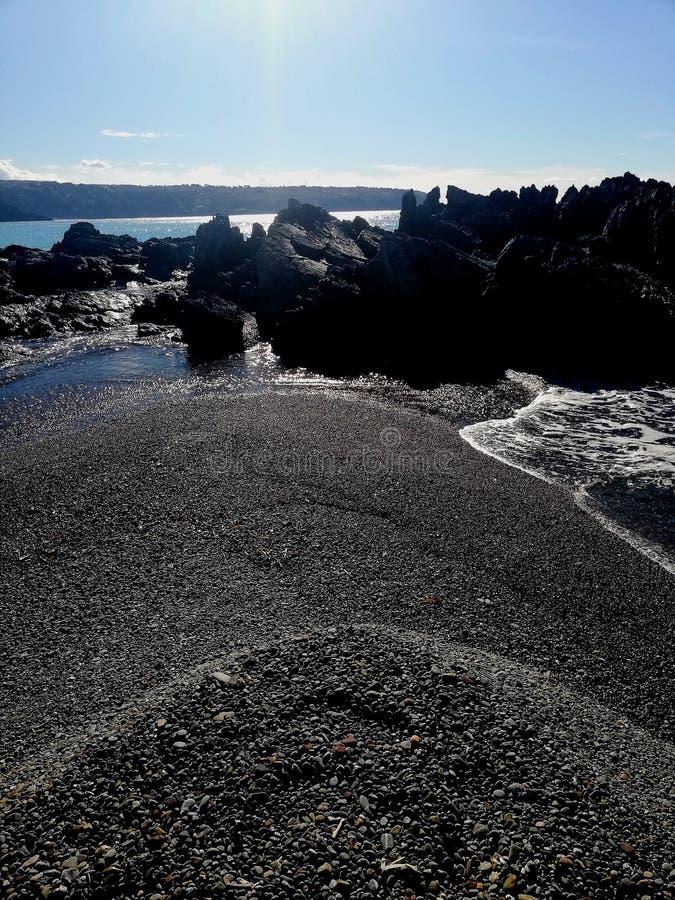 Rocce fra la spiaggia ed il mare fotografia stock