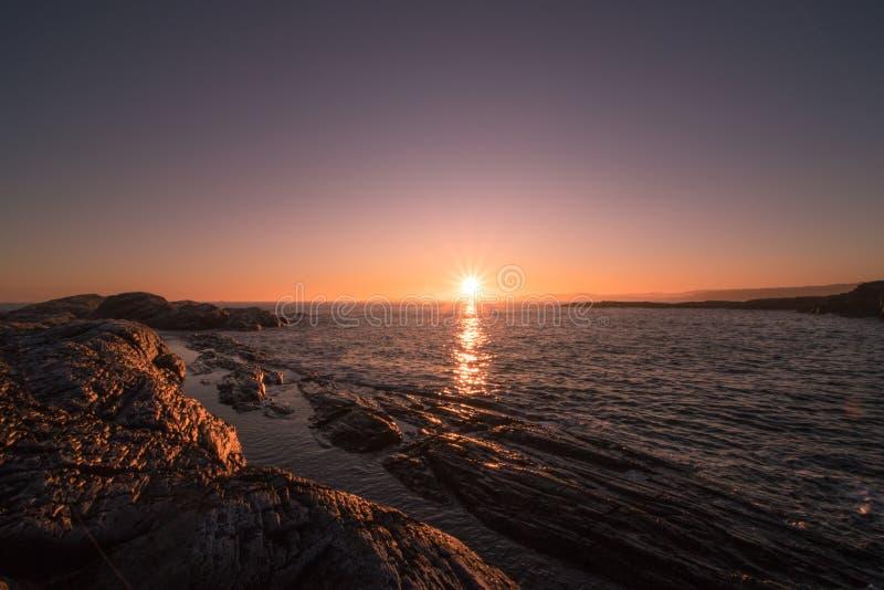 Rocce marroni accanto al corpo d'acqua durante il tramonto fotografia stock libera da diritti