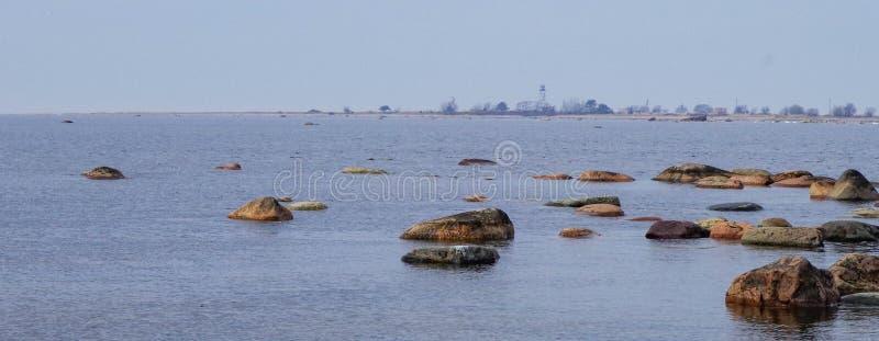 Rocce marroni sul corpo dell'acqua immagini stock libere da diritti