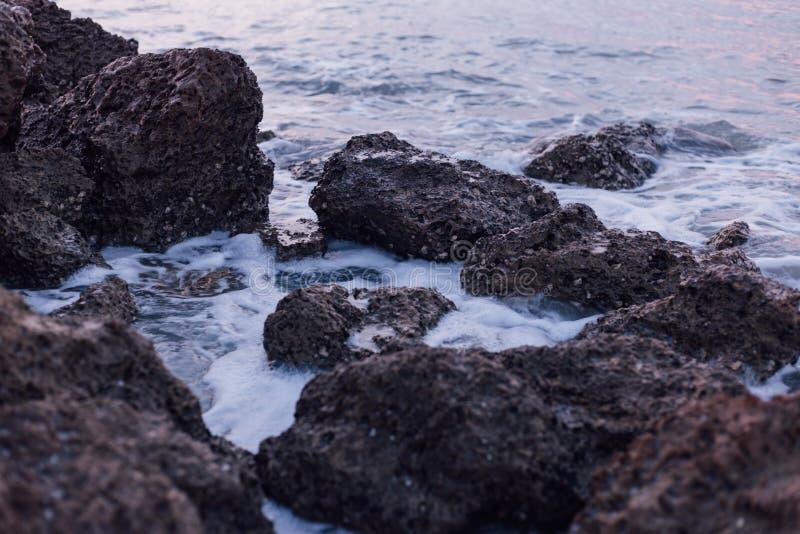 Rocce nere e marroni sul mare durante la luce del giorno fotografia stock